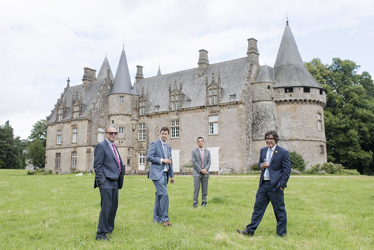 mariés et proches posant devant un château en Bretagne