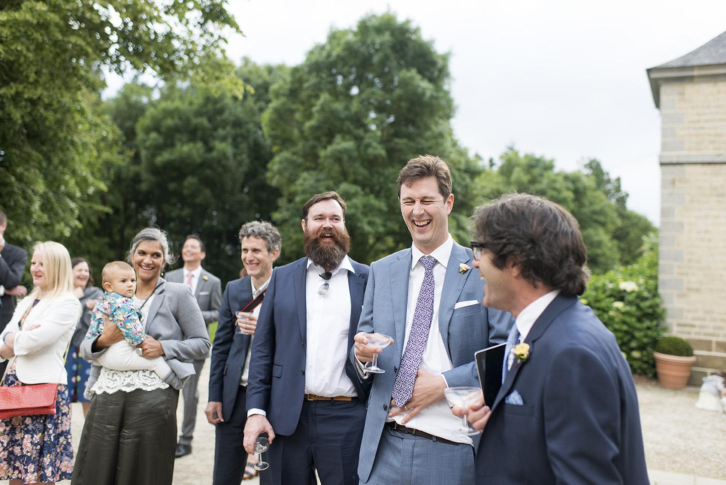 marié entouré d'amis riant lors d'un discours