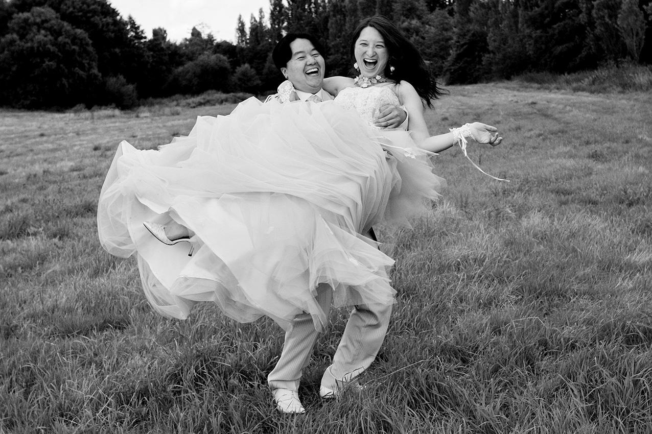le mari porte la mariée et tous deux rient dans un champ