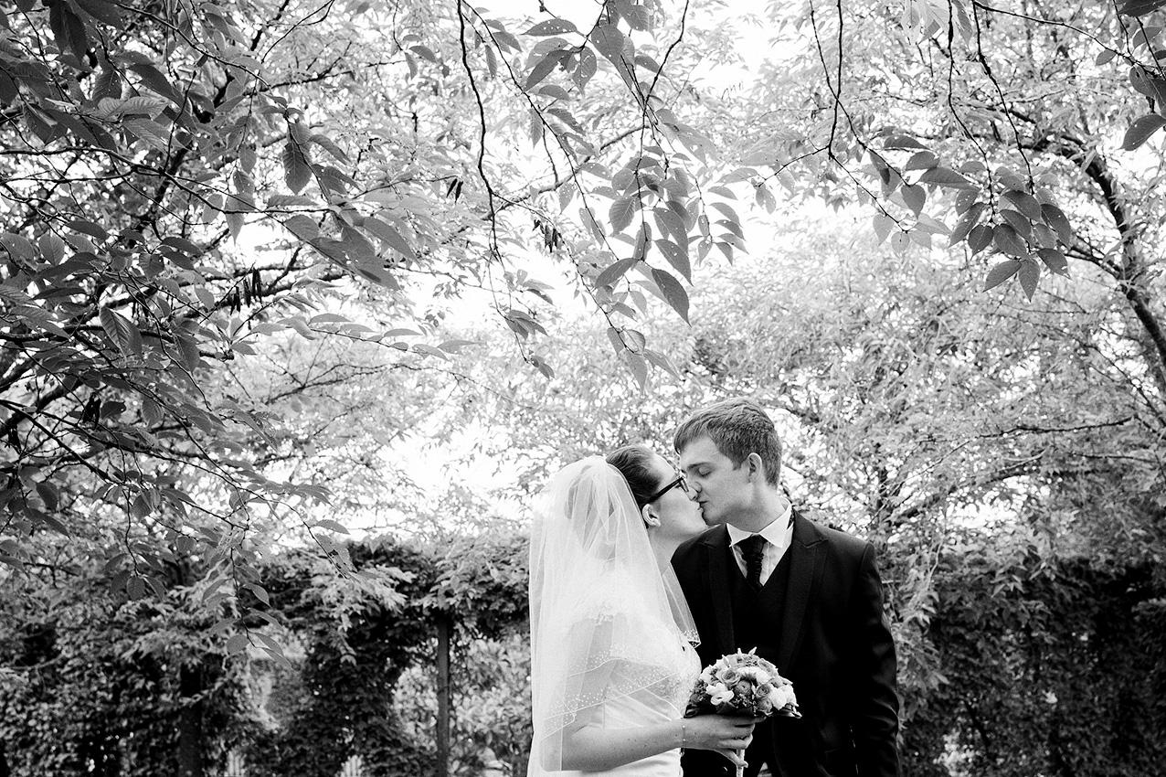 couple de mariés s'embrassant sous un arbre en noir et blanc