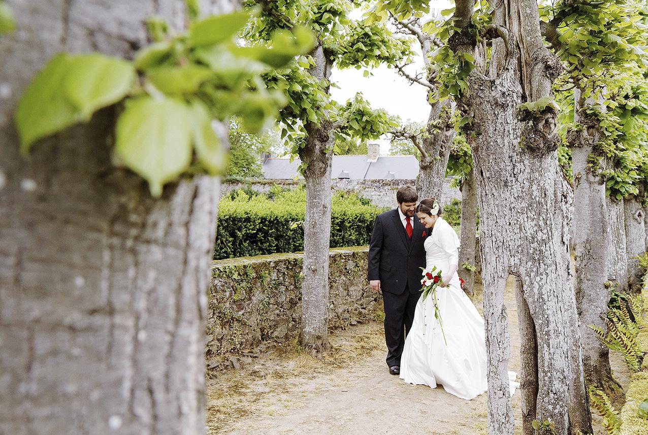 mariés posant dans une allée entourée d'arbres