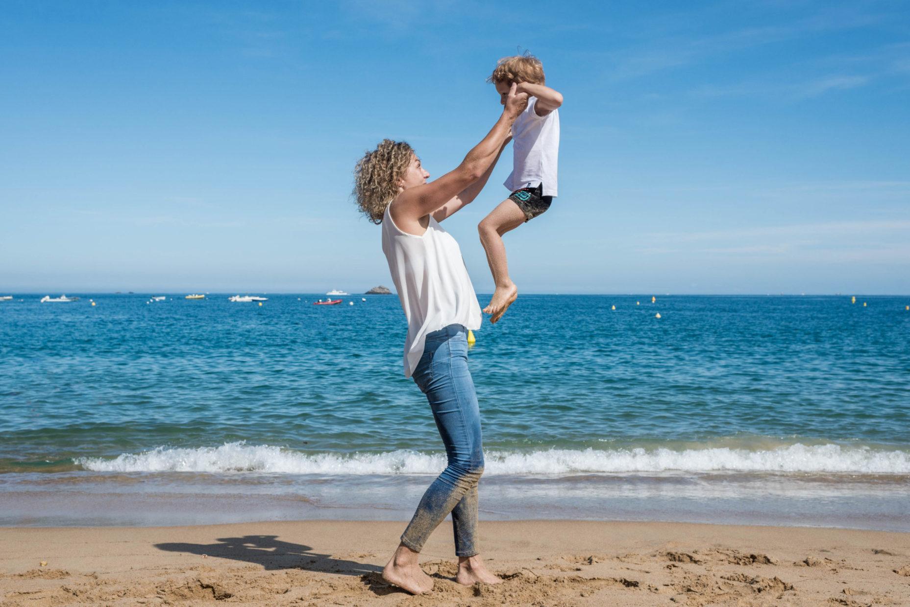 mère faisant sauter son fils en l'air devant la mer