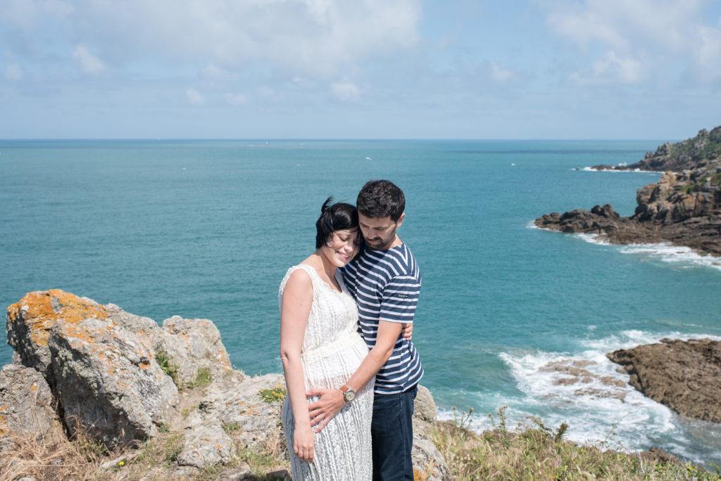 couple avec femme enceinte en robe dentelle devant la mer