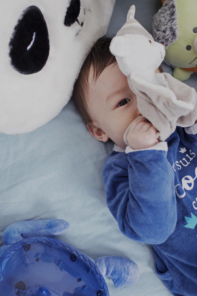 bébé se cache derrière son doudou