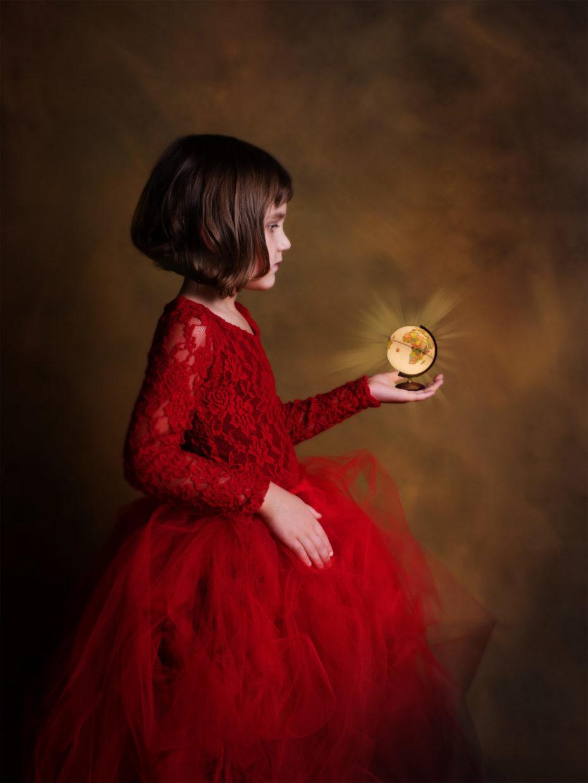 petite fille en rouge portant une mappemonde